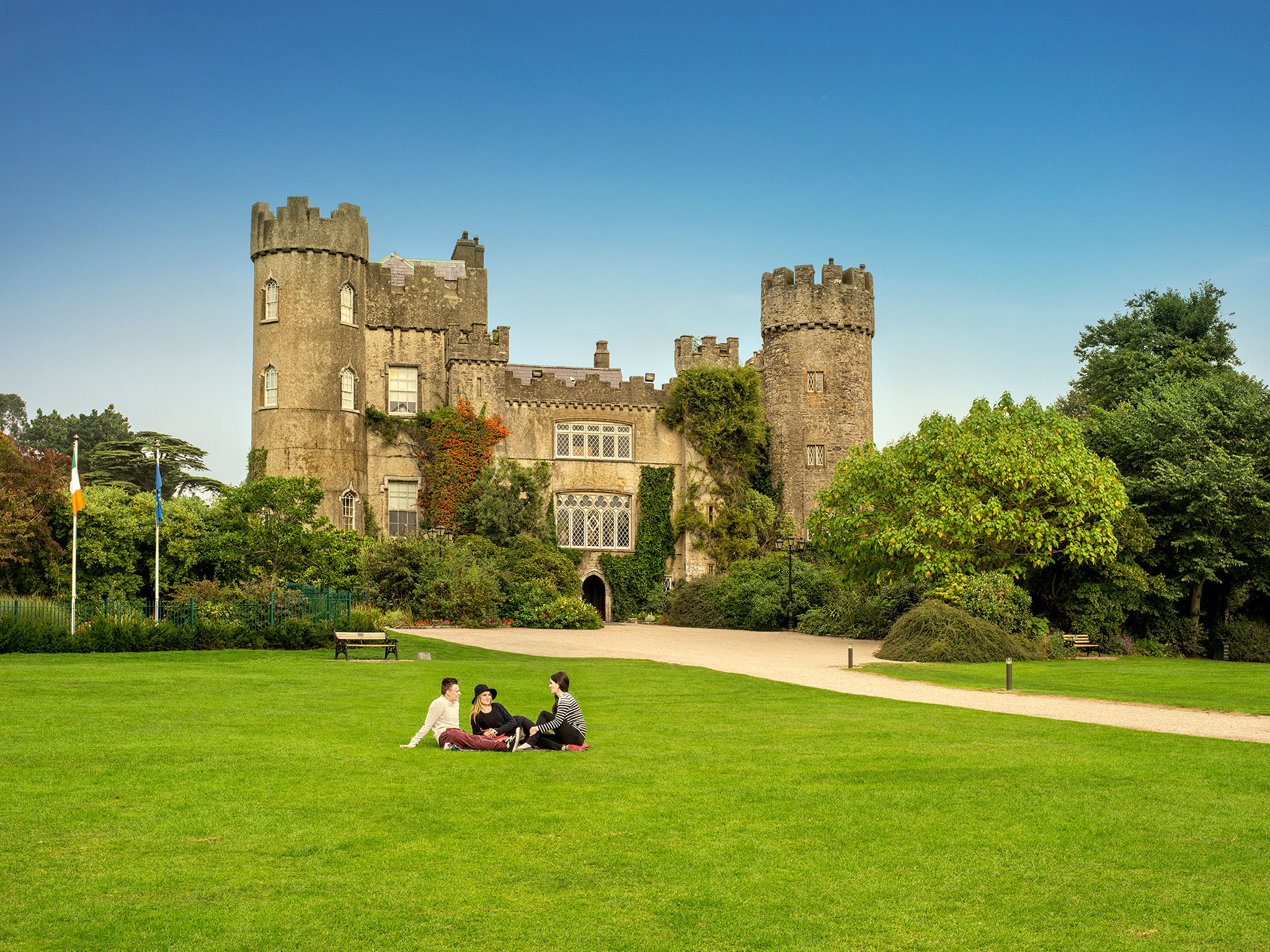 Historic Malahide Castle on sunny day, surrounded by open green spaces and trees.